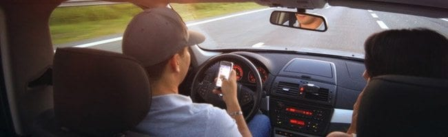 Man texting while driving on highway